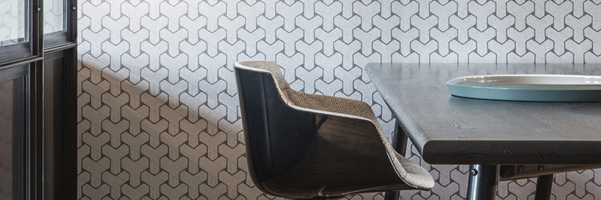Geometric designs on the wall behind a wooden chair.