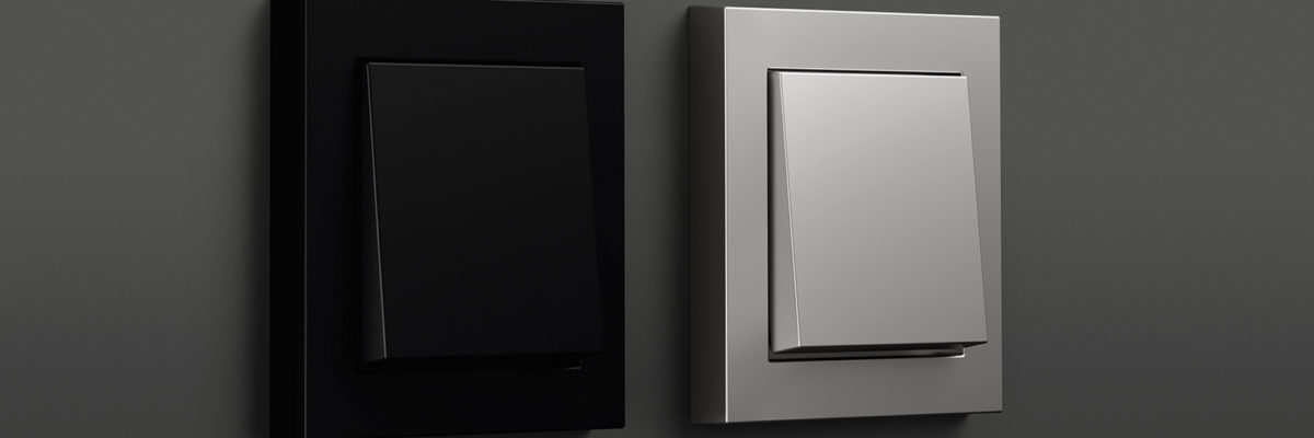 Two different stainless steel light switches on a dark background.