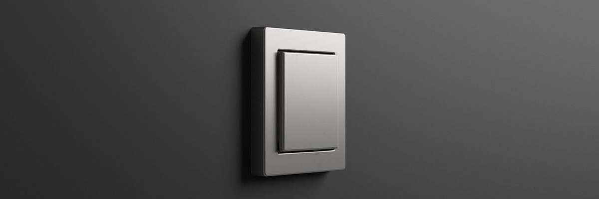 A stainless steel light switch on a dark background