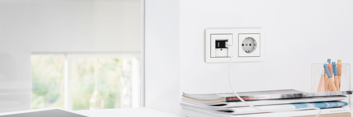 A white stainless steel light switch with integrated USB ports.