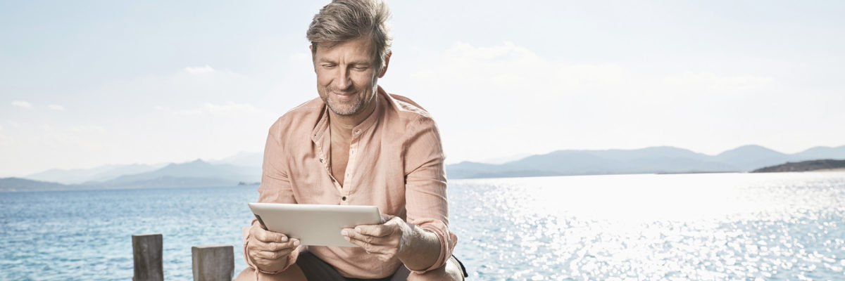 Man in front of sea holding a tablet computer.