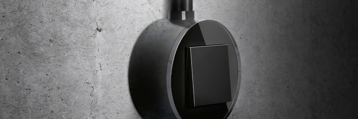 Gira Studio surface-mounted switch on rough concrete wall.