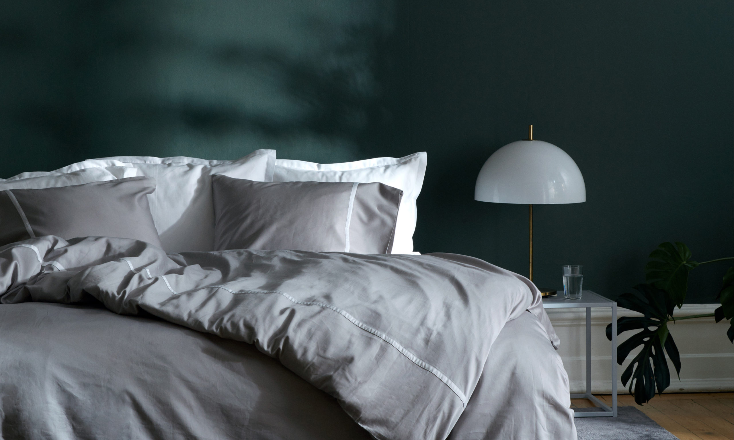 Bed with grey sheets against dark green wall