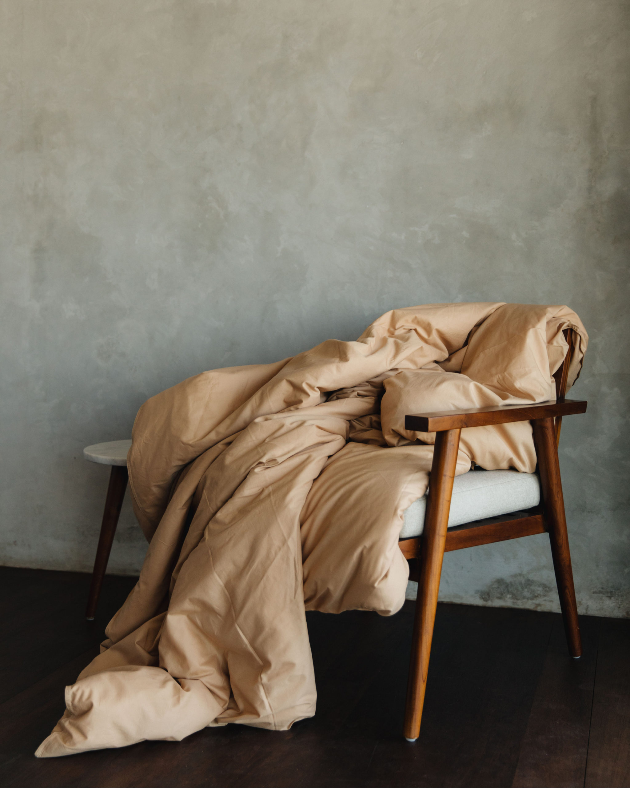 wooden chair covered by beige blanket